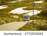 AURLANDSFJELLET, NORWAY - JUNE 27, 2018: Sunlight camper car with bicycles drive on mountains road. National tourist route Aurlandsfjellet with Norwegian Scenic Routes trademark logo sign - stock photo