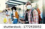 Small photo of Mixed-races young males and females people im medical masks standing in line at bus stop. Keeping safe social distance. African American stylish man tourist outdoor waiting for transport. Tourists.