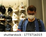 Small photo of Porto/Portugal- 10th July, 2020: A young Indian man is inside a fashion store. He is wearing a mask to abide new guidelines and lifestyle because of COVID-19 pandemic in Porto
