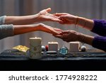 Small photo of Fortune teller woman reading palm lines during fortune telling, palmistry and divination