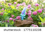 Small photo of cute troll on summer floral meadow. hasbro trolls, harper pinsel. concept of children's games, fun, toys