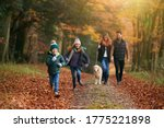 Family Walking With Pet Golden...