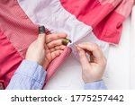 Small photo of The girl holds a needle and two thimbles in her hands. Vintage thimble. Sewing. Against the background of pink and white fabric.