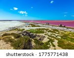 The Mediterranean coast of France, Camargue. Dark Pink Salt Water Bay. Salt production on the seashore. Huge truck rides along the bay with pink salt water. Concept of eco and photo tourism - stock photo