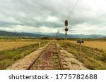 Old train track to the Alquife mine, there is a power line for the train and a traffic light, mountains and the sky is cloudy - stock photo