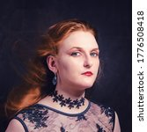 Small photo of Vamp woman in a black dress with hair swelling in the wind, portrait on a dark background. Halloween vampire girl face with red hair
