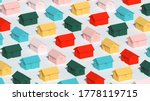 An array of simple small colorful rural houses on white background, town block abstract cgi representation, 3d rendering illustration