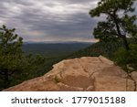 Evergreen trees are overhanging the edge of a rock outcropping, taken from FR 300 on the Mogollon Rim in Arizona.