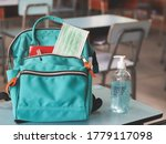 Small photo of COVID-19 prevention , back to school and new normal concept.Front view of backpack with school supplies ,surgical mask and sanitizer gel on school desk in classroom.