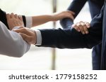 Small photo of Close up businesspeople connected arms standing side by side shoulder by shoulder show business protection, feel unity, corporate spirit save, strength of four, act together towards common aim concept