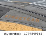 Asphalt and concrete street surface with metal streetcar rails, yellow streetcar sign and handicap ramp, horizontal aspect