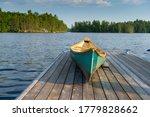 Green Canoe Sitting On A Lake...