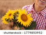 Smiling Woman Holding Sunflowe...