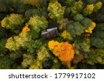 Aerial view of secluded cottage in the woods. Log cabin in the beautiful autumn forest. View from above. Colorful trees.