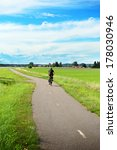 Bicycle, green fields and small village - stock photo