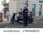 Small photo of Menton, France - July 2, 2020: A police officer writes a fine to two misplaced scooters