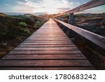 Deserted wooden boardwalk leading away through coastal dunes vegetation towards a glowing cloudy sunset sky in a moody evening landscape on Amrum, North Frisian Islands, Schleswig-Holstein, Germany