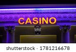Small photo of Illuminated casino red neon sign with purple wall, animation. Text casino neon light in dark night. Best neon casino promotions flicker, flash and flash color on blue background