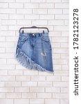 Small photo of Front view of Jean skirt, denim skirt, Mini, on hanging isolated on wall background. Female jeans skirt isolated against. Women\'s denim skirt.