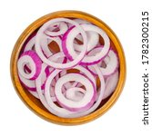 Small photo of Red onion rings in wooden bowl. Slices of the onion cultivar Allium cepa with purplish red skin and white flesh tinged with red. Closeup, from above, on white background, isolated, macro food photo.