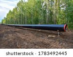 Small photo of Natural gas pipeline construction work in forest area. Installation of gas and crude oil pipes. Pipe on top of wooden supports at construction site. Construction of gas pipes to new LNG plant