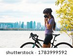 Small photo of Wearing covid-19 mask while riding bike. Sport cyclist woman biking putting on face mask for Covid-19 prevention during summer outdoor leisure exercise activity. Fitness outside.