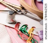 Small photo of Embroidery set fot cross stitching. White fabric, thimble, embroidery hoop, colorful threads, scissors and needls. On pink background.