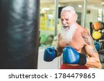 Hipster senior man boxing inside training fitness gym club - Mature fit boxer doing workout session - Sport, self defense and healthy lifestyle concept - Focus on nose