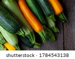 Small photo of A set of multi-colored zucchini yellow, green, white, orange on the table close-up. Food background. Fresh harvested courgette, cropped summer squash. Picked green courgettes. Still life in kitchen.