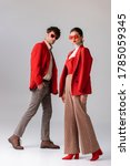 Small photo of full length view of fashionable couple in red blazers and sunglasses looking at camera on grey