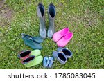 Small photo of Six pairs of old rubber boots of a big family stand on the grass. Short rubber country goloshes.