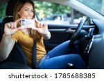 Small photo of Driving school. Young beautiful woman successfully passed driving school test. Female smiling and holding driver's license. Girl with driving license.