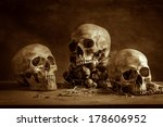 Small photo of Still life with human skulls and bunch of garlics on wooden table