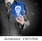 business man touching light of... | Shutterstock . vector #178717058
