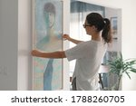 Woman Hanging A Painting At...