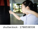 Small photo of Asian student girl is crying and raising fists,female people is punching into punch bag takes out her anger,emotional explosion,stress relief,feels angry,disappointed,self- loathing,catharsis concept