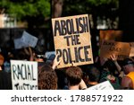 """Small photo of Washington, DC, USA - August 1, 2020: A protester carries a sign saying, """"Abolish the police,"""" at Lafayette Square / Black Lives Matter Plaza during the Demand DC protest and march"""