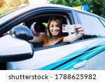 Small photo of Woman with driving license. Driving school. Young beautiful woman successfully passed driving school test. Female smiling and holding driver's license.