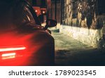 Automotive Theme. Exotic Car Night Drive in Dark Aged Urban Area Alley Close Up Photo.  - stock photo