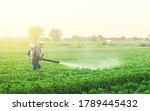 A Farmer With A Mist Sprayer...