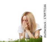 Small photo of Pollen allergy, woman sneezing in a field of flowers