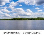 Vistula river landscape with other shore visible at horizon. Blue sky with white clouds. Sunny summer water landscape in Poland, Europe.