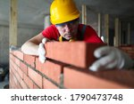 Small photo of Builder carefully puts red brick on the masonry. Quick work bricklayer. Guy measures level masonry. Man is building brick wall. Correctly calculate material. Builder manually carries brick structure