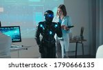 Small photo of Female robotics engineer control automated robot with digital tablet giving commands. Multi-ethnic team of researchers working in high tech scientific laboratory.