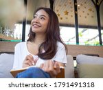 Small photo of Young Asian woman or a writer sitting in a journal or writing a novel in a coffee shop outside the office. Freelance women are relaxing writing jobs. Asian women, beautiful women, Writers.
