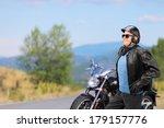 Mature Biker Walking In Front...