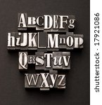 Alphabet photographed using a mix of vintage letterpress characters on a black, textured background. - stock photo