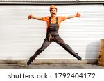 Young happy laughing caucasian man builder construction worker in a safety helmet is jumping in front of the roller door lifting gates. Copy space for you text and logo. Industry concept