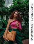 Small photo of Fashionable curly woman wearing pink asymmetric ruffled top, green trousers, holding straw wicker top handle bag, posing in tropical garden. Summer fashion, lifestyle, beauty conception