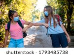 Small photo of Two Teenage Girls say hello touching hands elbow meeting in the Park on the way to School. New handshake due to Coronavirus pandemic safety protective behavior